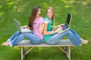 Teenage girls with laptop computers